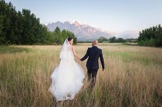 Bride and Groom Walking in Field at Cape Town Wedding Venue by Lauren Kreidemann Photography